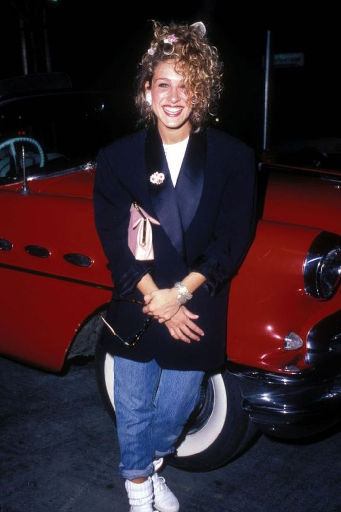 80s fashion trends, Sarah Jessica Parker, young blonde woman with curly hair tied in a messy ponytail, over-sized blazer and baggy jeans, white shoes and socks