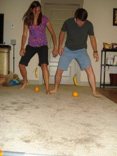 How's is Hanging..tie a banana to a string around your waist..knock it into the orange to move orange across room