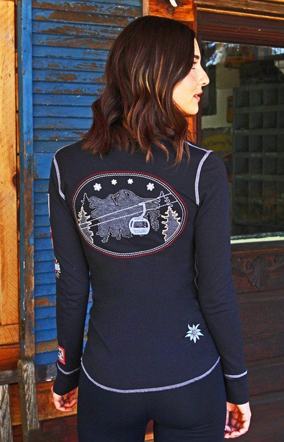 Be mountain ready with this whimsical alpine themed ski lift Henley. Exquisite gondola detailing adorned with three snow and ski styled patches down the arm and three delicate snowflakes on the front.75% Cotton 25% Polyester double faced fabric.