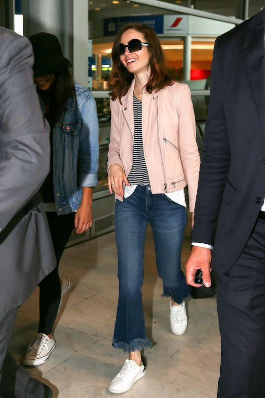 Lily Collins in a pink moto jacket, navy and white stiped shirt, kick flare jeans in a dark wash with fringe hem, oversized sunglasses, and white adidas sneakers