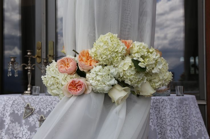 Fresh Roses and Hydrangeas used to gather fabric and lights around posts