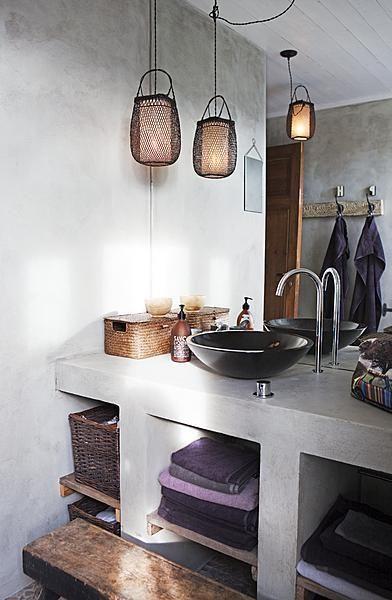 In deze badkamer zijn de muren ingesmeerd met cement en waterdicht gemaakt met olie. De bijzondere lampen en rieten manden geven de ruimte een sierlijk gevoel. De wasbak is gemaakt van basalt.