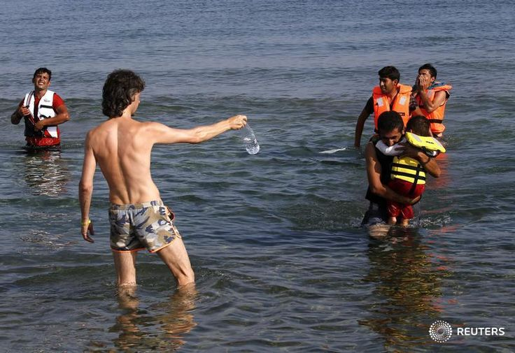 """Tourist offers water to exhausted Iranian migrants """"landing"""" on Kos by dinghy from the Turkish coast. Yannis Behrakis"""
