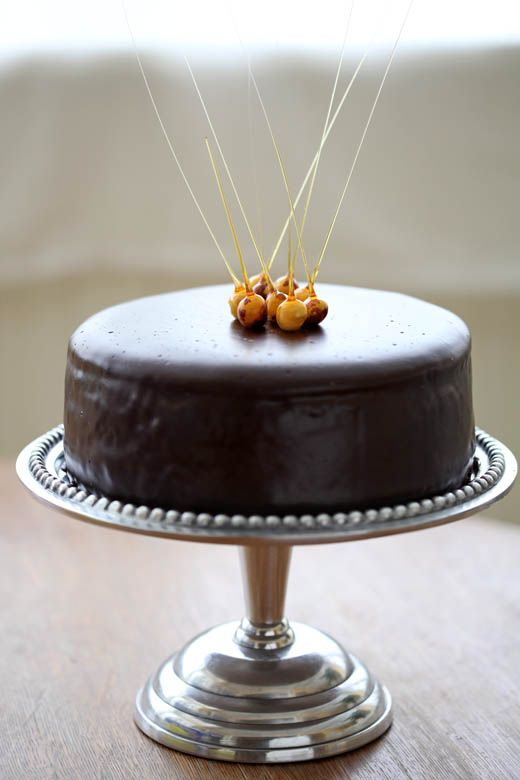 Chocolate Ganache Glazed Praline Cheesecake with Candied Hazelnuts | recipe from Zoe Bakes