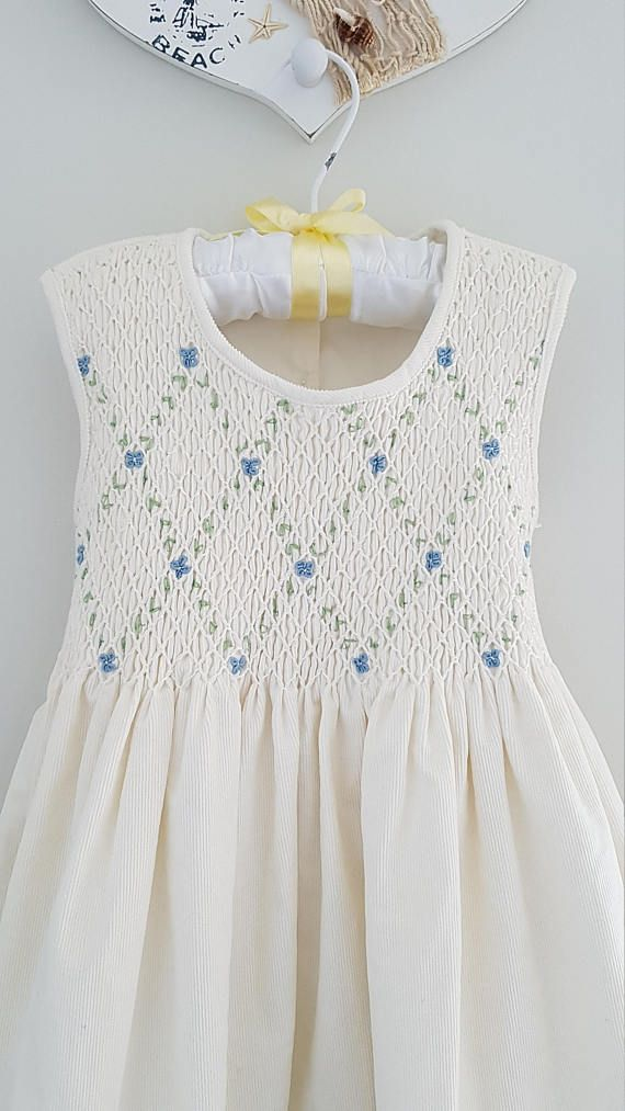 This beautiful dress has been made with a fine pinwale white corduroy which is perfect for winter months paired with a cardigan or jacket. The bodice has been elegantly hand smocked.The back closes with buttons and a tie back waist. Would suit a little girl who is 5-6 years of age. Size 5 Chest measurement 26 Length from back of neckline to hem 25