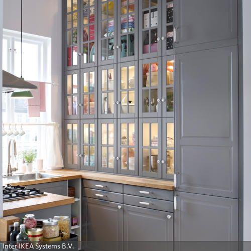 Die Schrankwand im Landhausstil reicht bis zur Decke. Durch das Glas der Schranktüren sind Geschirr und Küchenutensilien in verschiedenen Farben sichtbar. So wirkt…