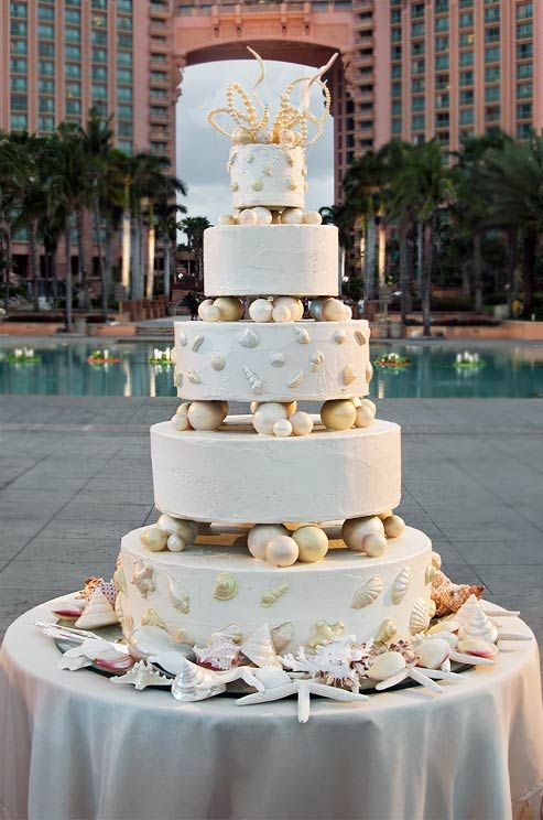 The towering #wedding cake is decorated with seashells, starfish and giant sugar pearls.