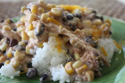 Aztec Chicken  8 Large Chicken Breasts  3/4 t Cumin  2 Garlic Cloves, minced  4 C Frozen Corn  2 C Salsa  2-15 oz. cans Black Beans, rinsed & drained  16 oz. Cream Cheese, softened & cubed   Combine cumin, garlic, & salsa in a small bowl. Add corn & beans; stir well. Put with Chicken in crock pot. Cook on high about 6 hrs. Add cubed cream cheese & allow to melt. Shred chicken & return to crock pot just before serving. Serve over cooked rice, with cheddar cheese & crumbled tortilla chips.