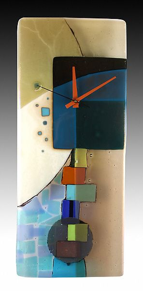 The Andrea pendulum clock is quietly layered in french vanilla, teal, overlapping blues and iridescent bronze. Colorful juxtaposed blocks play hide and seek with the pendulum behind.