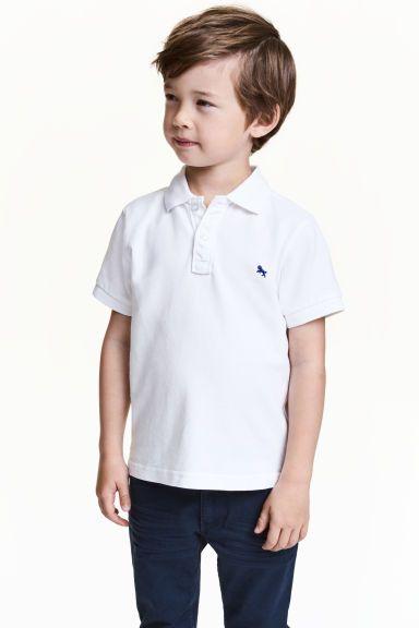 Polo: Polo à manches courtes en piqué de coton. Modèle avec col côtelé, boutonnage en haut et petite broderie sur la poitrine. Un peu plus de longueur dans le dos et petites fentes latérales.