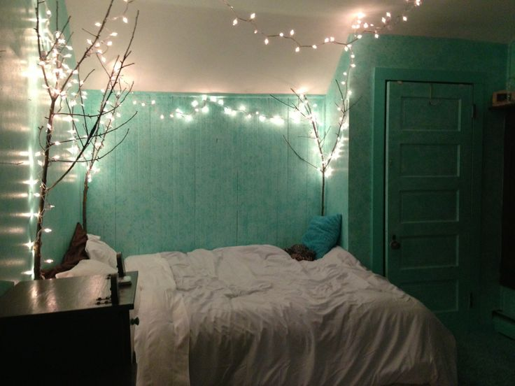 Lovely bedroom with turquoise walls and dark brown and white accessories. Tree branches with twinkling fairy lights are a lovely idea. This just screams lovely - and it seems actually do-able !