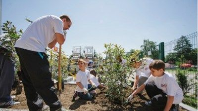 Sustainability Week in Serbia with children planting shrubs