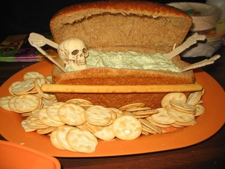 """Dead Man's Dip--Want a memorable dip presentation on your buffet table this Halloween? Here is an awesome """"coffin"""" filled with dip and a little skeleton nestled inside. Using a firm loaf of bread and a skeleton found almost anywhere this time of year, you can make this yourself. Fill with Lipton's famous spinach dip or your own favorite, and you have a snack to """"die"""" for!"""
