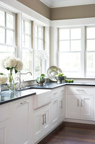 khaki walls, farmhouse sink and white shaker kitchen cabinets with honed black granite counter top.
