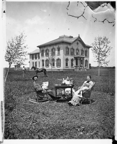 A family, possibly that of William Bonner, is posed around a table in a yard. Behind them is a man with a horse and behind him a large Victorian brick house with rounded windows, curved shutters and brackets on top and porch top. The house is now located on the east side of Hwy 151 about one mile north of the intersection with county highway A. in Trenton, Wisconsin. (Photo circa 1871.)