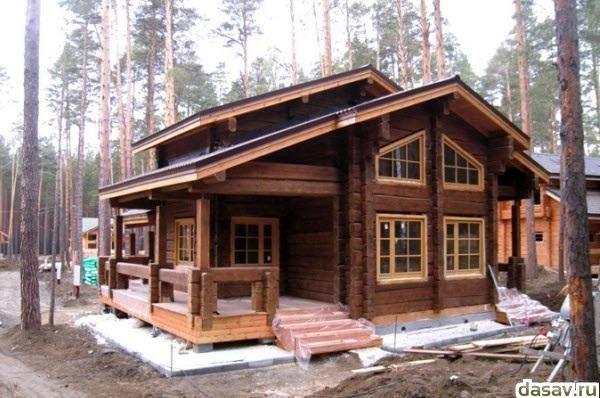 Деревянные дома из оцилиндрованного бревна и лафета зимой