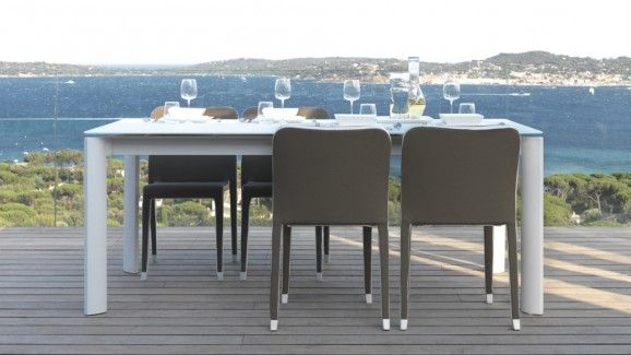100% Made In Italy. An extendable rectangular table designed by Marco Acerbis. It has a lacquered aluminium frame, available in white or dove grey. The top is made of opaque tempered glass.