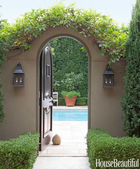 A vine is pruned to enhance an arched doorway in a wall separating the pool and terrace.