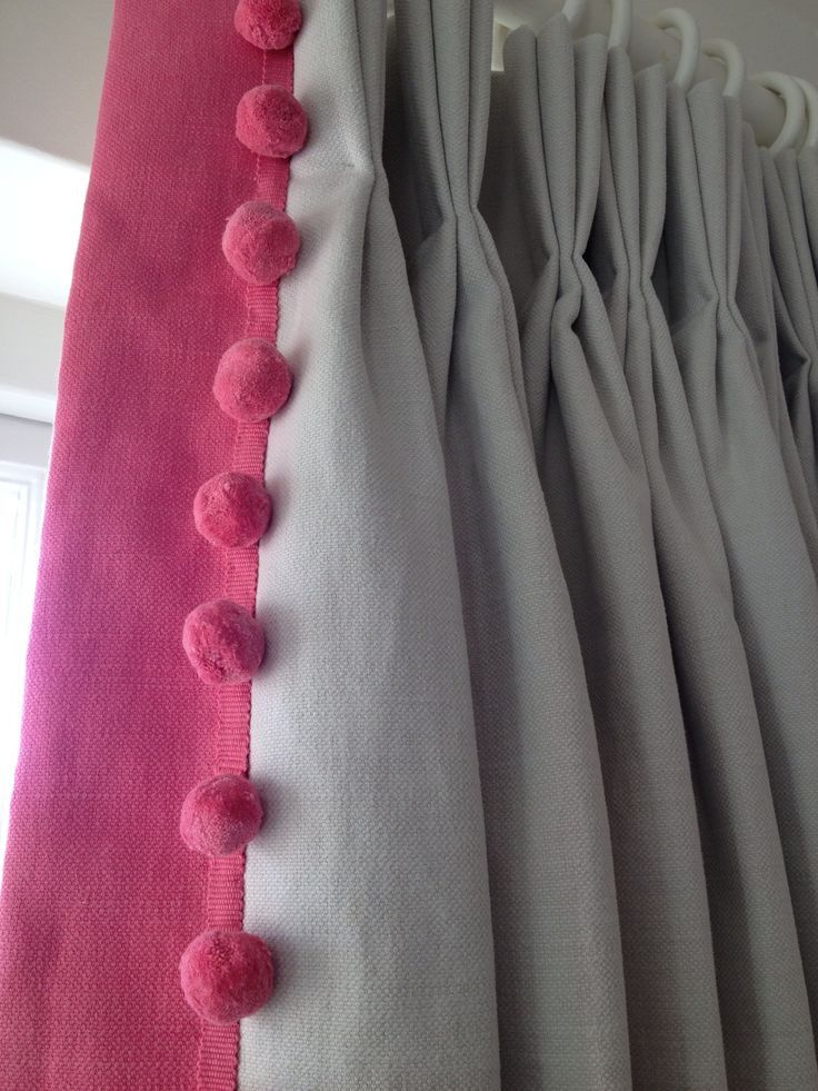 Soft grey linen curtains with a hand pleated heading and a bright pink contrast edge with pink pompom trimming. By Clare Laughland Interiors