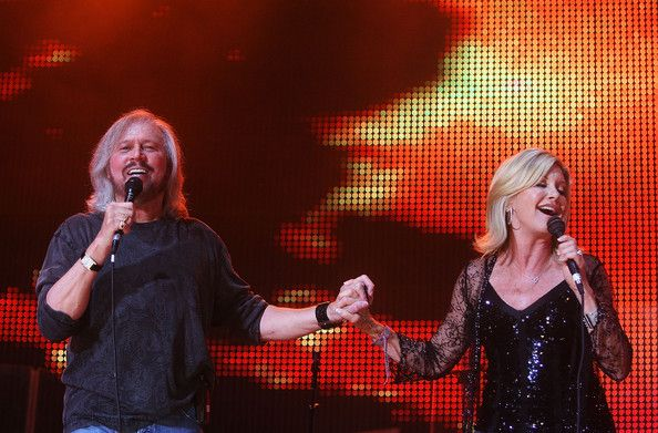 Barry Gibb Photos - Barry Gibb and Olivia Newton John perform on stage during the Sound Relief concert at Sydney Cricket Ground on March 14, 2009 in Sydney, Australia. The Melbourne and Sydney simultaneous concerts have been organised to raise funds for victims of the recent Victorian bushfires and Queensland floods, with profits split equally between the two causes.  (Photo by Mark Metcalfe/Getty Images) * Local Caption * Barry Gibb;Olivia Newton John - Sound Relief - Sydney