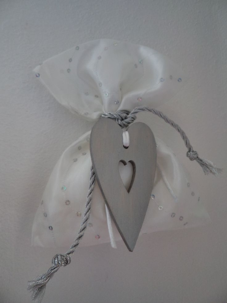 Satin pouch with tiny silver tinsel and a wooden heart painted in silver colour.