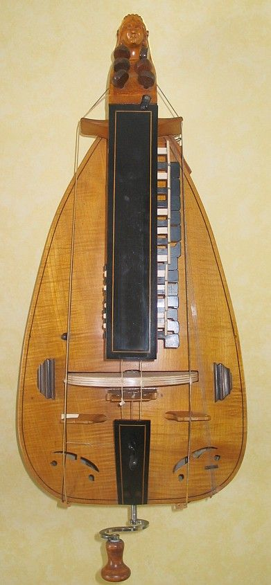 "Hurdy Gurdy (also known as the wheel fiddle), The strings are sounded by a wheel which the strings pass over. Its functionality can be compared to that of a mechanical violin, in that its bow (wheel) is turned by a crank. Its distinctive sound is mainly because of its ""drone strings"" which provide a constant pitch similar in their sound to that of bagpipes."