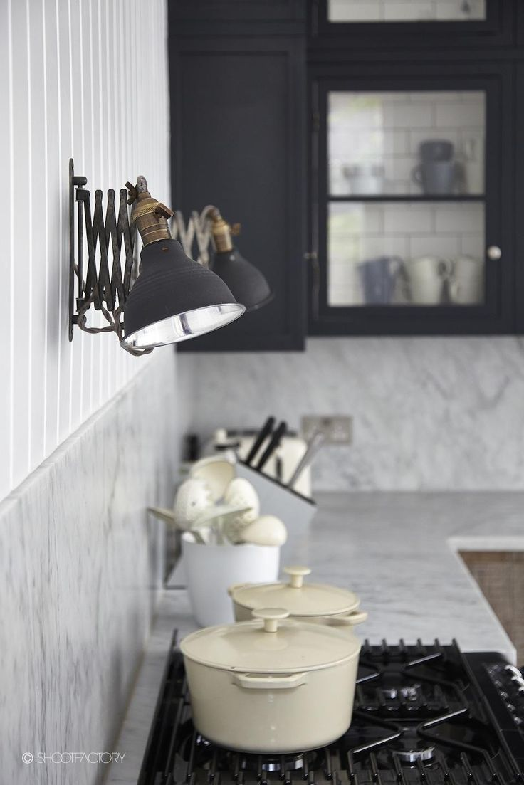 Rustic industrial kitchen, panelled, marble work surface, metro tiles, exposed brick, filament bulbs, tongue and groove, scissor lights, AGA, white AGa, herb trough, wood effect tiles, ercol, la Creuset, ceiling beams, copper tap, movable island. Photographed by Malcolm Menzies ww.82mm.com Kitchen by http://blakeslondon.com