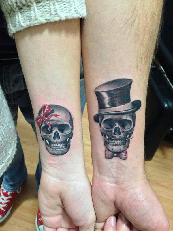 Skull inspired couple tattoo. The grayscale tattoos are inked on the wrists signifying that one is a male and another is a female skeleton with the red ribbon on the head. It looks comical and at the same time unique.