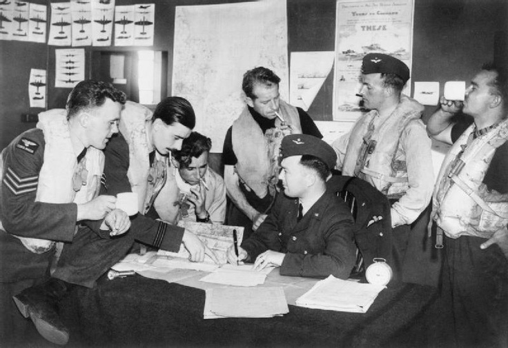 Czech pilots of No 310 (Czech) Squadron, based at Duxford, being interrogated by the Intelligence Officer after a sortie.