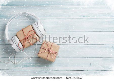 Christmas music gift concept. Headphones and gift boxes on wooden table. Top view with copy space