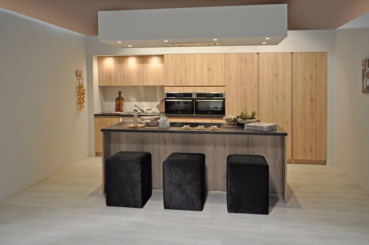 Greeploze keuken met houten kookeiland. De houtstructuur van deze moderne keuken geeft een warm gevoel. De keuken is voorzien van kolomkasten, ingebouwd keukenapparatuur en een gootsteen aan de muur. Daarnaast is er ook nog een kookeiland met kookplaat. Boven het kookeiland hangt een luifel met ingebouwde dampkap. De stoffen poefs passen perfect bij het design van de toestellen en de donkere kleur van het laminaat werkblad.