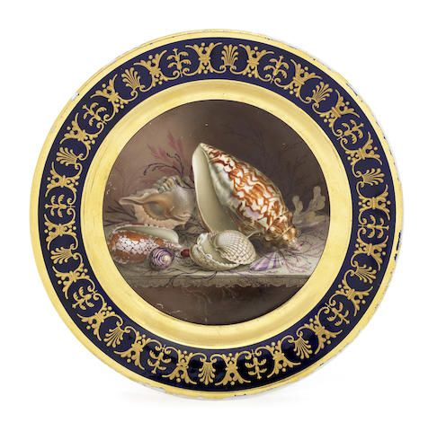 A Worcester (Flight, Barr and Barr) cabinet plate by Thomas Baxter, circa 1815 The cavetto fully painted by Thomas Baxter with a still life of six shells, naturalistically painted and arranged on a stone shelf amongst corals and seaweed, surrounded by a thin black line and a wide gold band, the blue border with a classical design in raised gold, 24cm diam, impressed crown and FBB, printed mark referring to Royal patronage