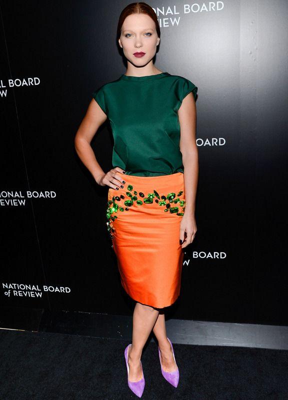Todo una mezcla de colores la de este look de Prada colección Primavera 2014 que luce la actriz francesa Lea Seydoux con una blusa de seda en verde botella con falda naranja con detalles joya también en verde. Tal vez hubieramos cambiado los salones lila por unos nude, pero el resultado final nos convence.