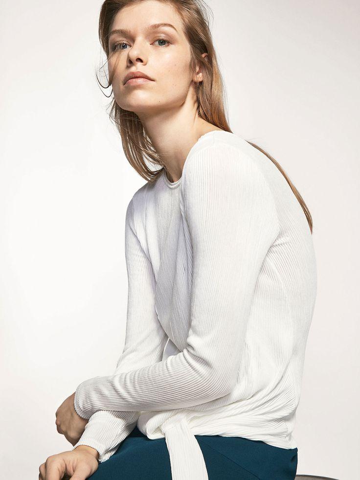 T-shirt plissada, confecionada numa delicada mistura de tecidos. Corte reto, gola redonda, manga comprida e parte inferior com nó ornamental.
