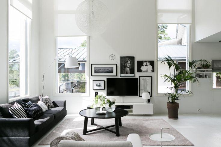 Olohuoneen sisustus on skarpin mustavalkoinen, tunnelmaa pehmentävät runsaat tekstiilit ja viherkasvi.