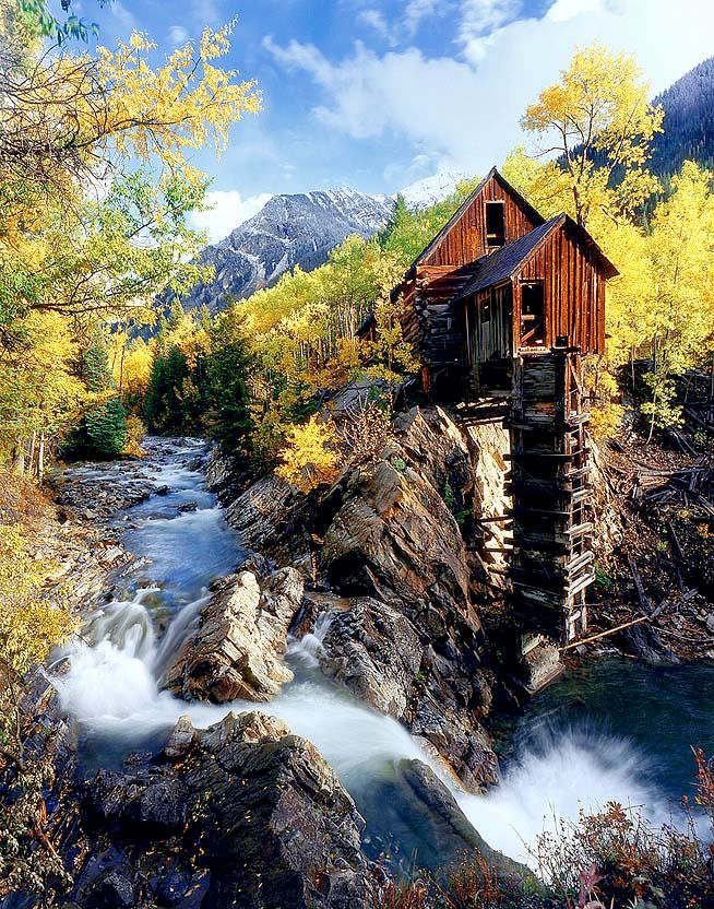 Dilapidated Log Cabin Atop A Cliff In The Mountains By A
