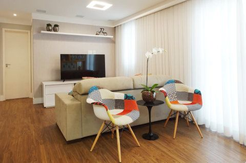 Duas cadeiras Dkr Patchwork, de base de Madeira, assinada pelo designer Charles Eames, trazem cor para o ambiente.