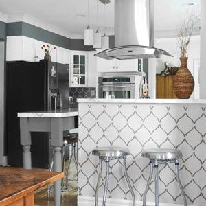 A gray-on-white stencil pattern on this dining-area divider mirrors the white-on-gray stenciling in the kitchen beyond.   thisoldhouse.com
