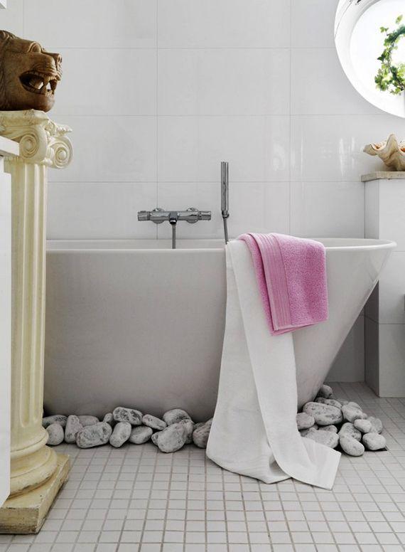 Modernes Badezimmer Mit Weißen Mosaik Bodenfliesen, Rundem Fenster Und  Freistehender Badewanne Weiß Mit Weißen Steinen Als Dekoration
