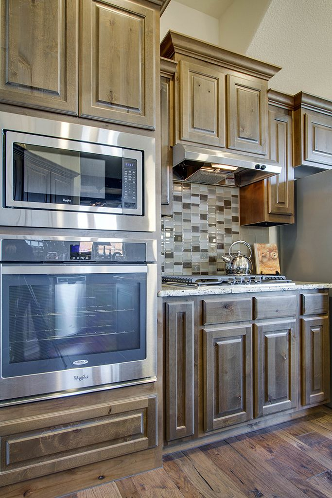 Gehan homes kitchen medium brown cabinets tile for Brown kitchen cabinets with black appliances