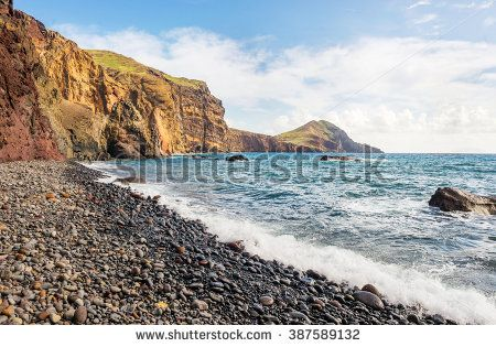Volcanic black pebble beach with turquoise blue ocean water, high cliffs and blue sky during sunny day. Located on north coast of Ponta de Sao Lourenco, the eastern part of Madeira Island.