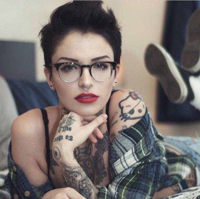Pixie cut, septum piercing, horned glasses, tatoos, classic makeup, and plaid.
