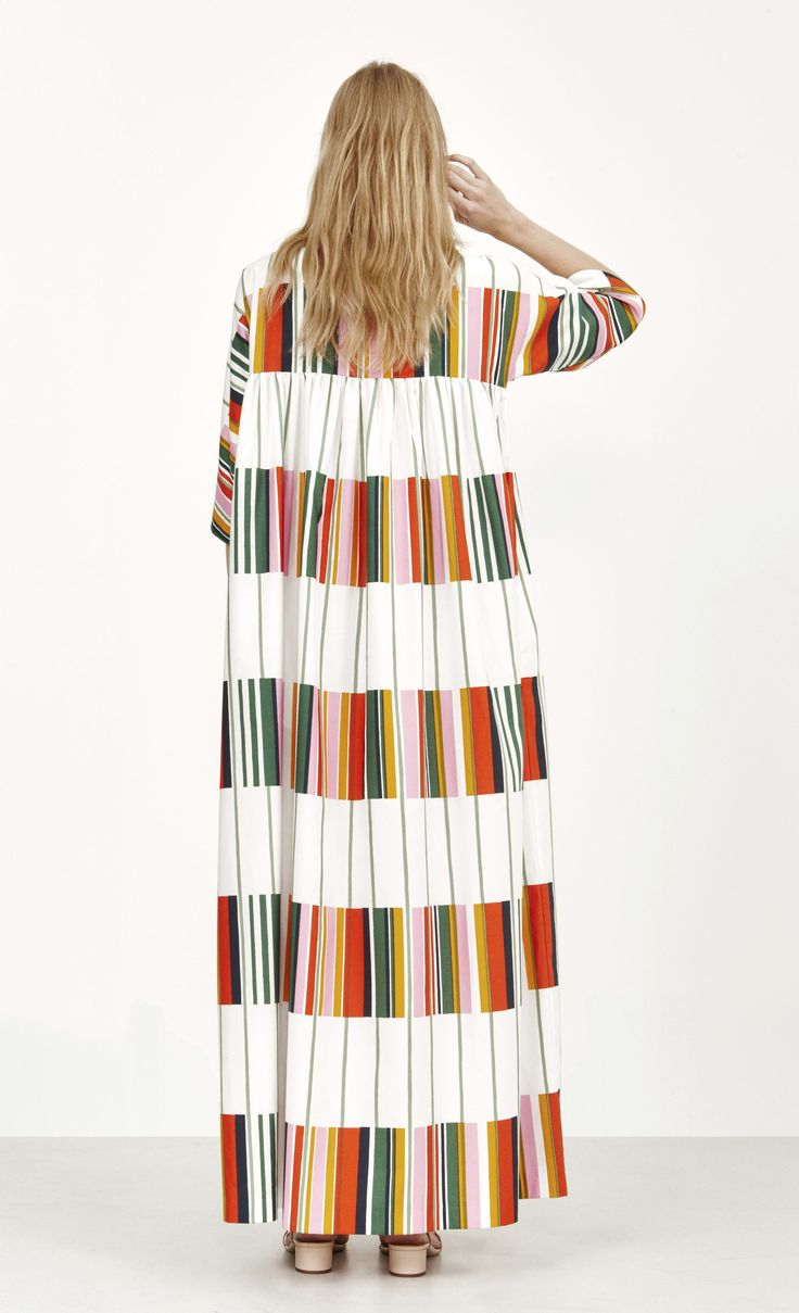 A long dress made of woven cotton featuring the Kirjo print designed by Pentti Rinta. Gathers run across the front and back horizontal yoke seams giving a loose, full cut to the ankle hemline. Details include loose sleeves that fall just past the elbow an