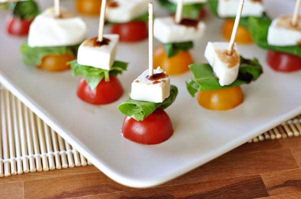 Caprese Skewers 1 pint cherry tomatoes, red or yellow 1 bunch basil leaves (about 18-30 leaves, the big ones can be cut in half) 8 ounces fresh mozzarella cheese Balsamic vinegar, for drizzling 2-3 dozen long toothpicks/skewers