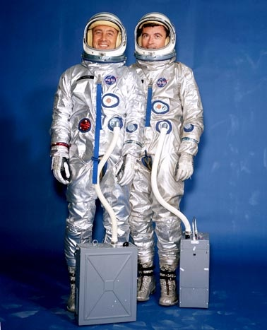"""roject Gemini  1962-1966  The David Clark Company, which won the bid to produce suits for the X-15 """"spaceplane,"""" went on to make suits for NASA's second manned space program, Project Gemini. In March of 1965, Gus Grissom (left in image) and John Young were the first astronauts to fly a Gemini mission. Here, they pose in Gemini G2C training suits. The boxes at their feet are portable air conditioners."""