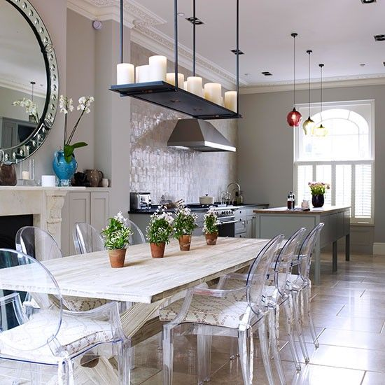 Open-plan kitchen with grey walls, neutral floor tiles, green freestanding island unit and long wood dining table and plastic chairs