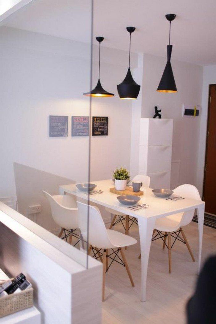 chaises blanches en plastique blanc, lustres noirs, mur blanc