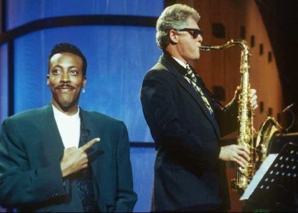 Arsenio Hall pointing at Bill Clinton playing the sax.
