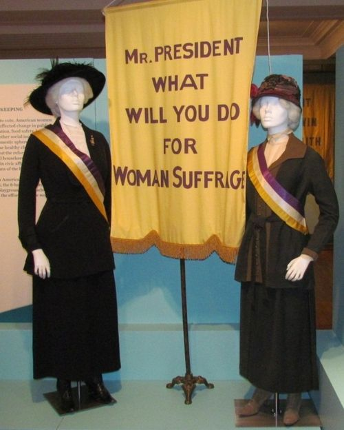 Two manikins on display at the Daughters of the American Revolution Museum represent the White House Picket Line vigil kept daily by members of the National Woman's Party (organizers of the March 1913 parade) starting in February 1917. Suits and hats, courtesy Shippensburg University Fashion Archives and Museum; Sashes and original banner pole, courtesy the Sewall-Belmont House and Museum; reproduction banner.