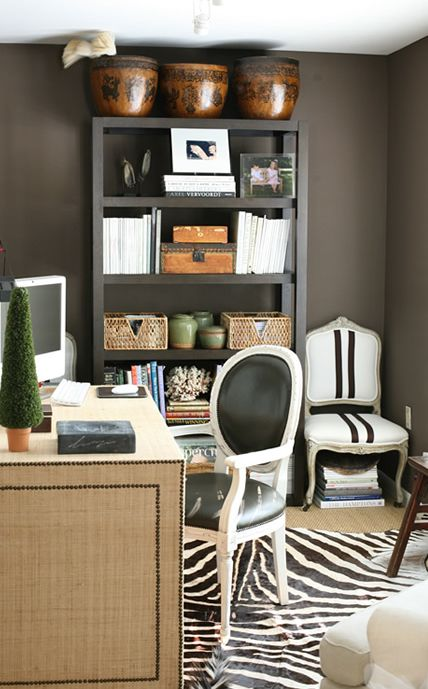 Chic taupe office design with rich taupe gray walls, black bookcase, zebra cowhide rug, linen desk with nailhead trim, white & black striped French chair and  black vinyl louis chair.